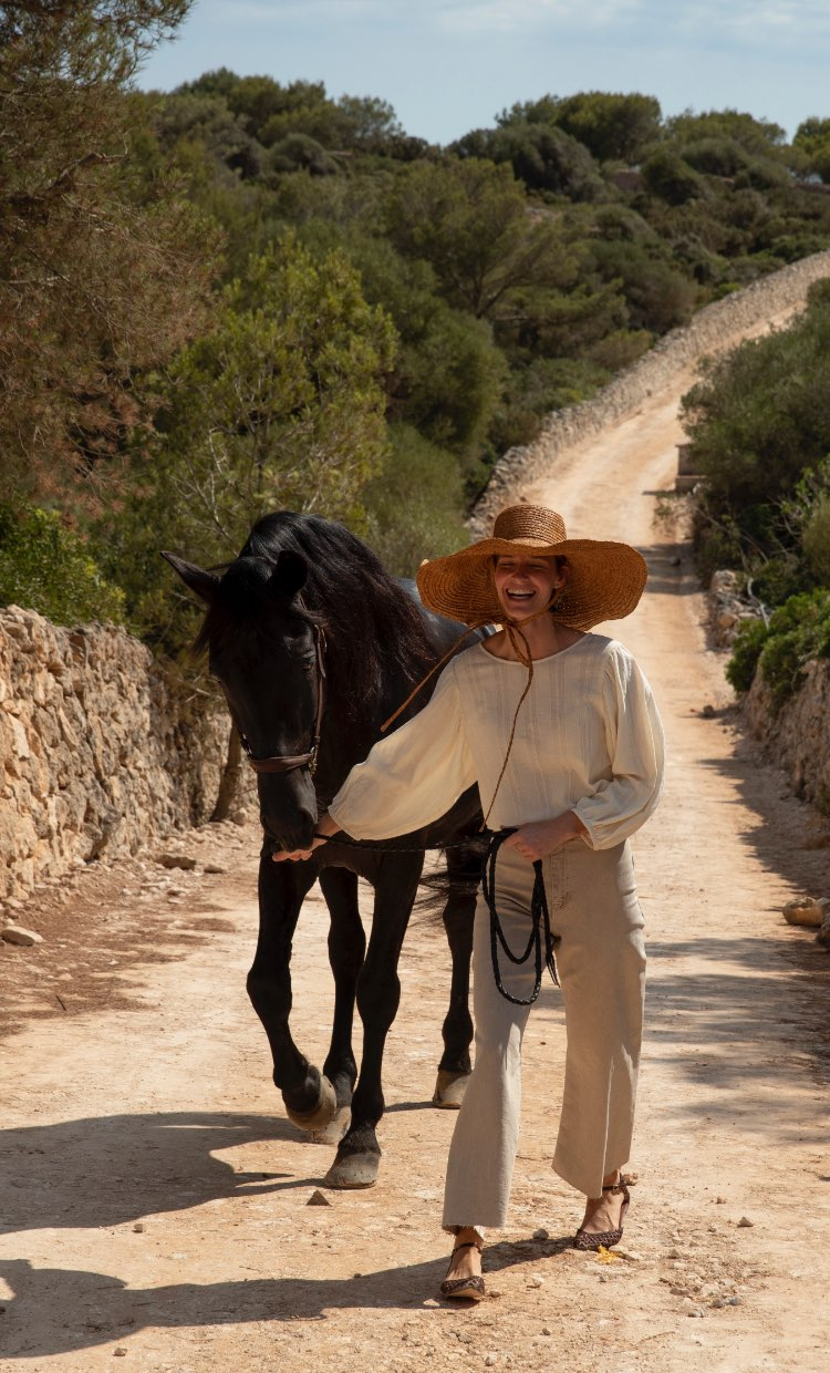Smiling woman leading a horse over an old portugese road.