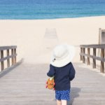 Child walks towards sunny beach